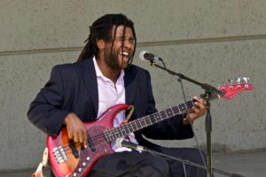 bearded, wearing a suit, singing playing bass