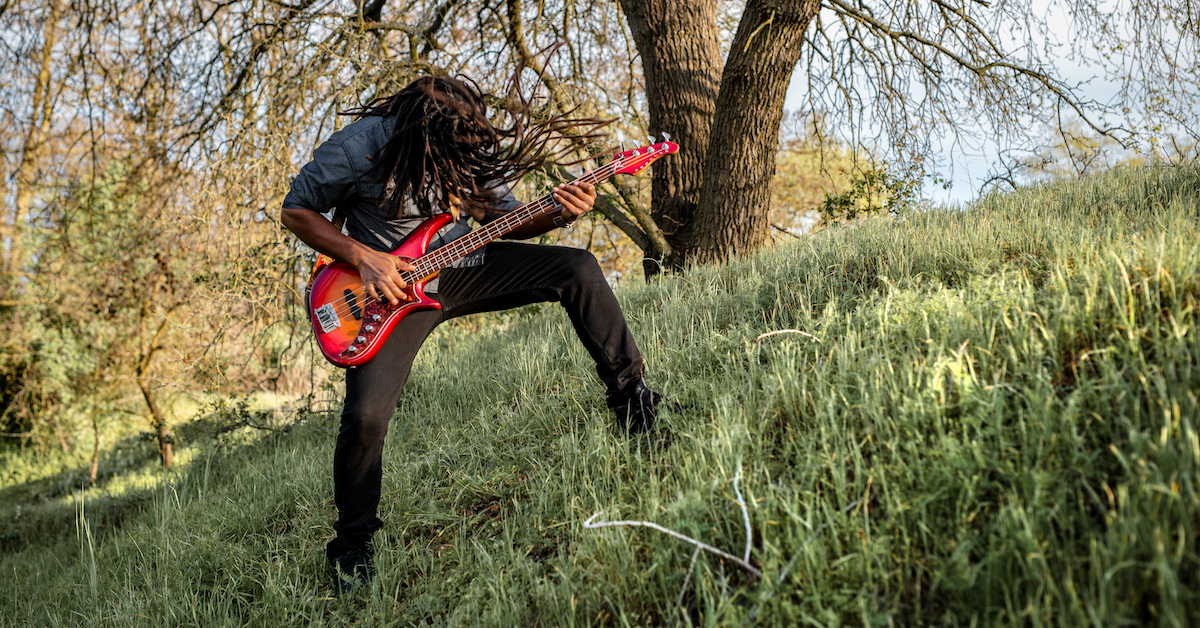 headbanging playing bass on a hill