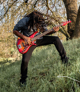 Headbanging dreadlocks on a grassy hill play a cherry sunburst pedulla bass guitar